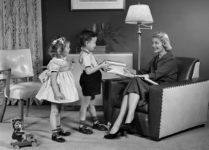 1950s Little Boy And Girl Son And Daughter Giving Woman Mother Sitting In Living Room A Gift Present